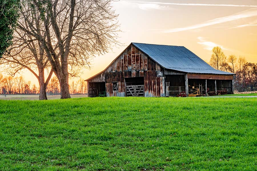 About Our Agency - Old Rustic Barn on Farm at Sunset
