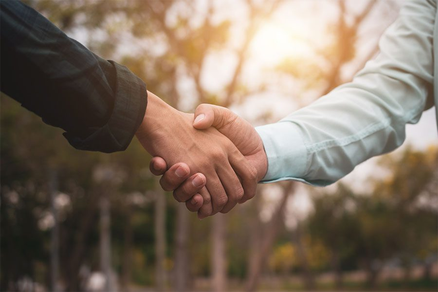 Refer a Friend - Two People Shaking Hands Outdoors