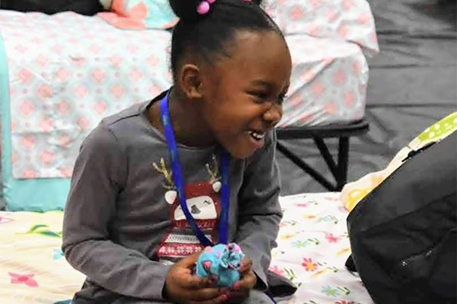 Community Involvement - Portrait of Excited Girl Sitting on Bed with New Toy During Sleep Dreams Event