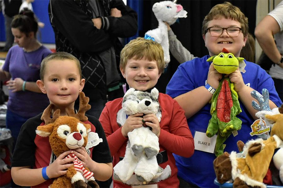 Community Involvement - Row of Happy Children Posing With Their New Stuffed Animal Toys During Sleep Dreams Event