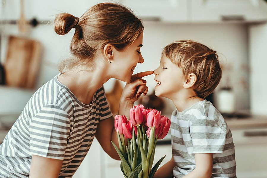 Nominate-A-Mother-Contest-Young-Happy-Mom-Laughing-with-Her-Son-As-He-Hands-Her-Pink-Tulips-for-Mothers-Day