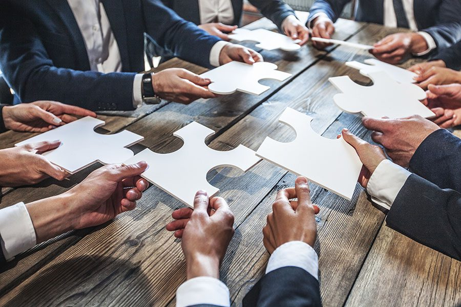 About Our Agency - Group Of Businessmen Holding Up Puzzle Pieces On Table