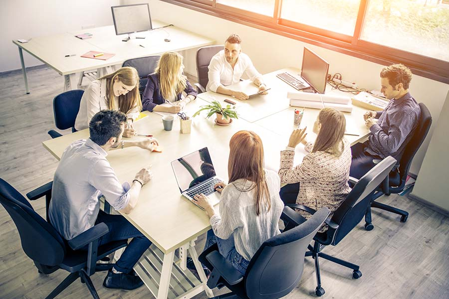 Business Insurance - Group Of Employees Sitting At Table Discussing Business Agenda