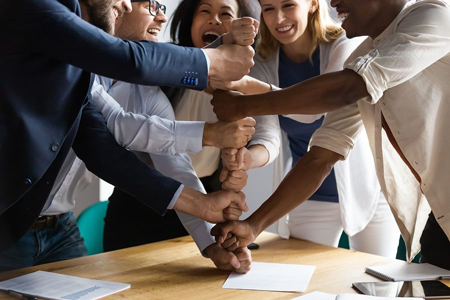 Employee Benefits - Group Of Employees Stack Hands Together On Table In Office