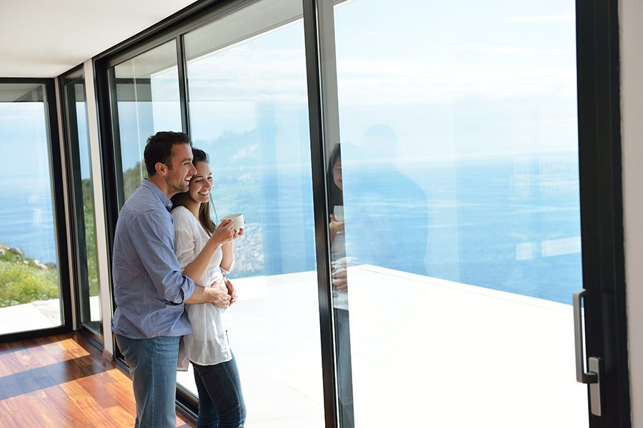 Client Center - Smiling Couple Looking at the Ocean From Their Modern Home