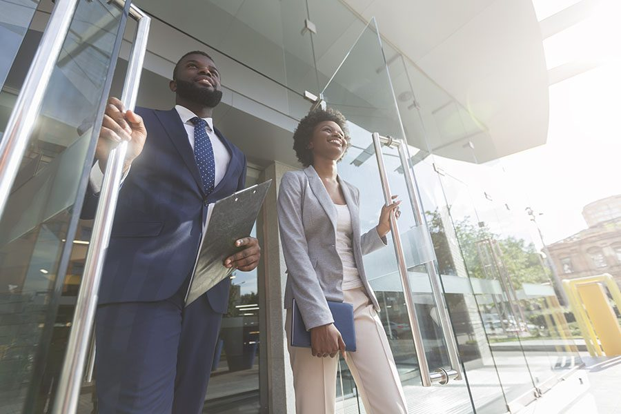 Employee Benefits - Two Employees Walking Out of Modern Business Building