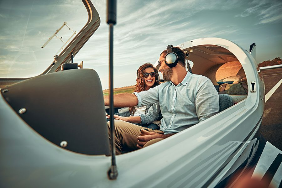 Private Aviation Insurance - Young Couple Having Fun Flying a Plane