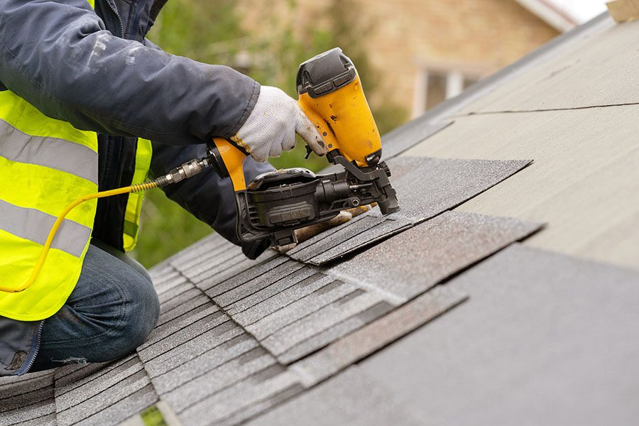 Request Certificate - Worker Using Nail Gun To Install New Shingles On Roof