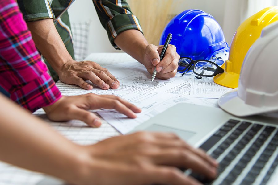 Specialized Business Insurance - Contractors at Desk with Laptop and Blue Hard Hat