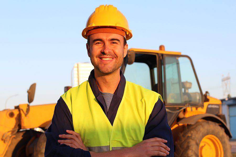 Contractor Insurance - Construction Worker Smiling with Arms Crossed and Looking at Camera Wearing Hard Hat and Construction Site in the Background