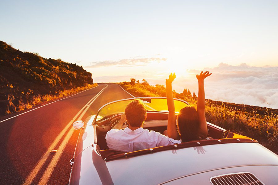 Personal Insurance - Couple Driving Down a Road in a Vintage Convertible Car and Female Rider Has Her Arms Raised at Sunset