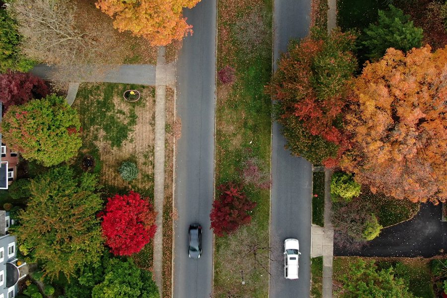 Ligonier, Pa - Suburban Residential Area with Two Lane Road Aligned with Colorful Trees in Autumn Foliage in Neighborhood with Aerial View