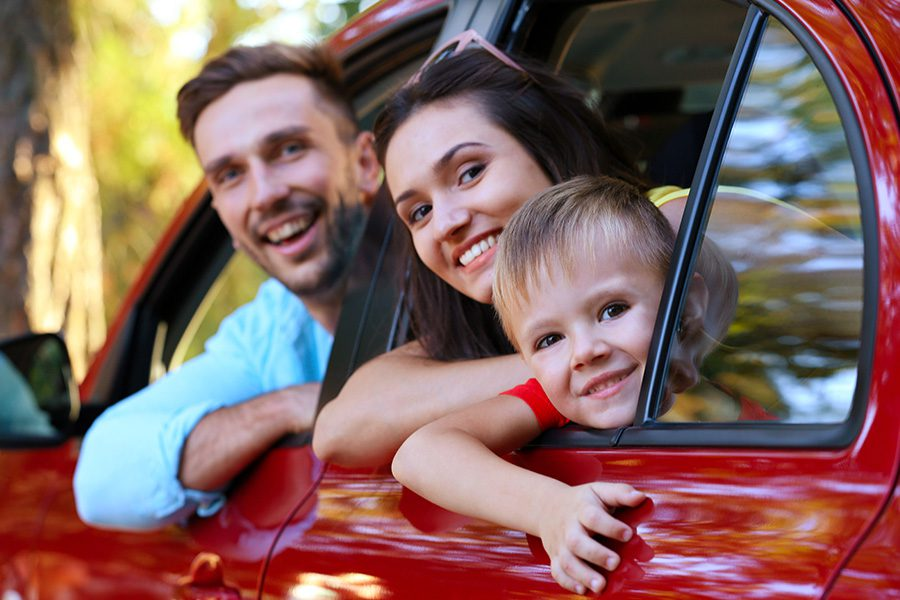 Personal Insurance - Happy Family with SonLooking Out the Window of a Red Car on a Sunny Day