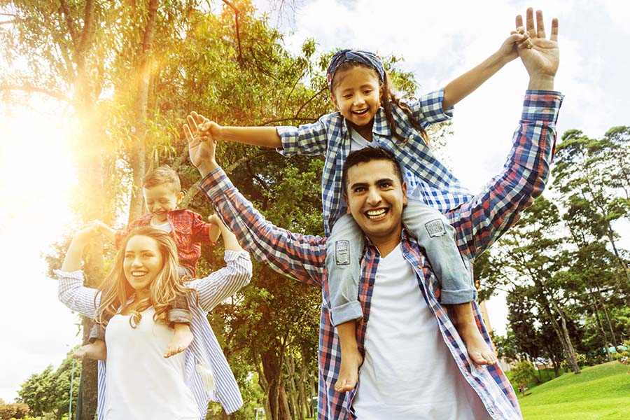 Blog - Young Parents Giving Their Kids Piggyback Rides At The Park