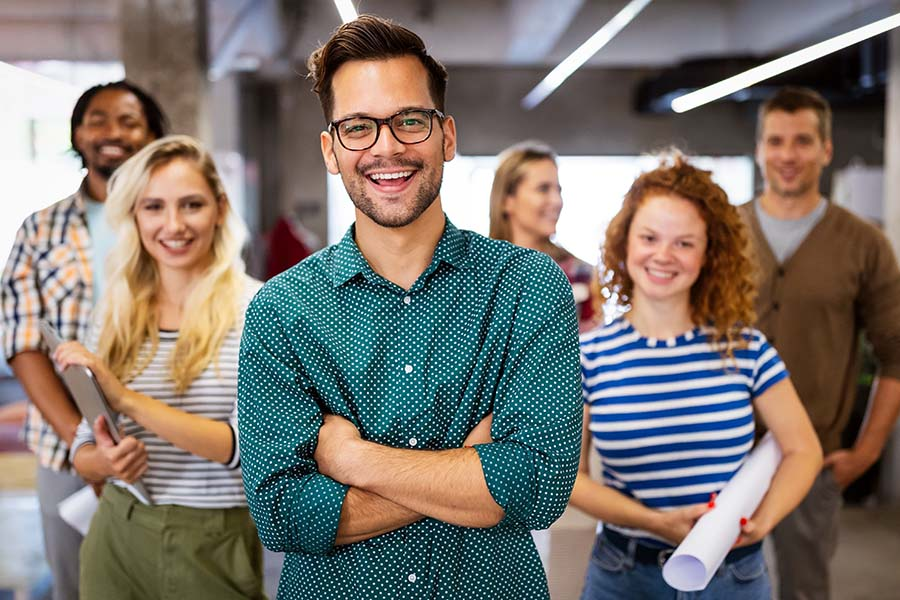 Employee Benefits - Group Of Smiling Employees Standing In Office