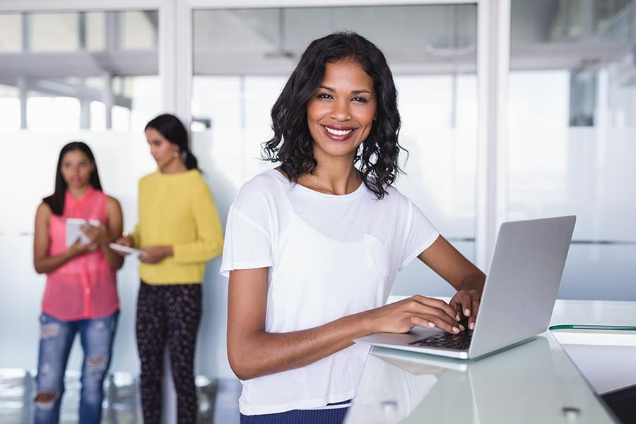 Business Insurance - Businesswoman Uses Her Laptop at a High Counter, Smiling at Camera, as Employees Work Behind Her