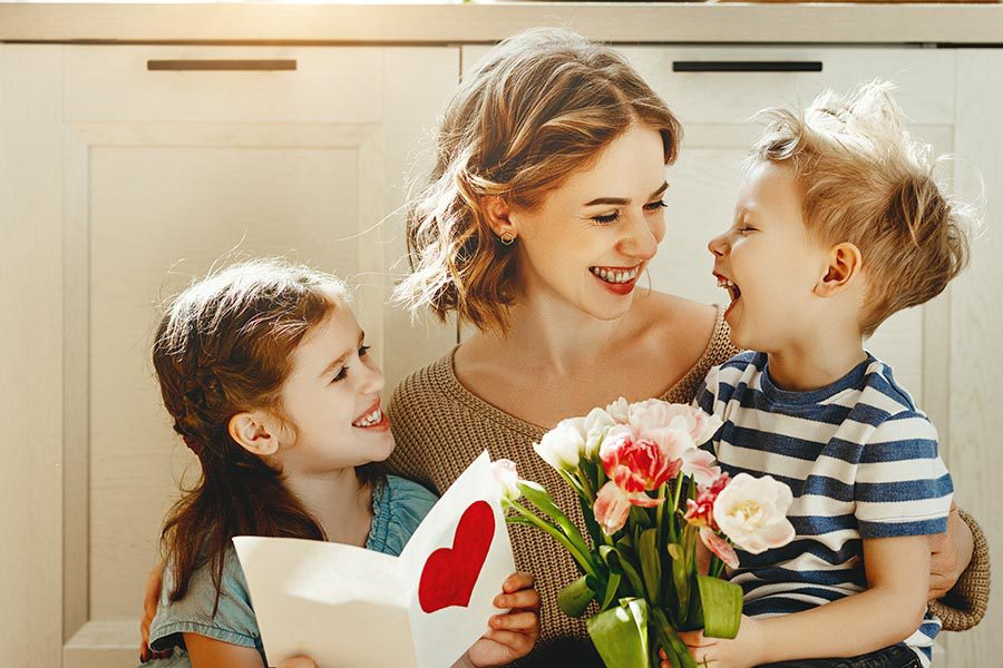 Personal Insurance - Mother Sits on the Kitchen Floor With Her Two Small Children Who Have Just Given Her Flowers and a Card