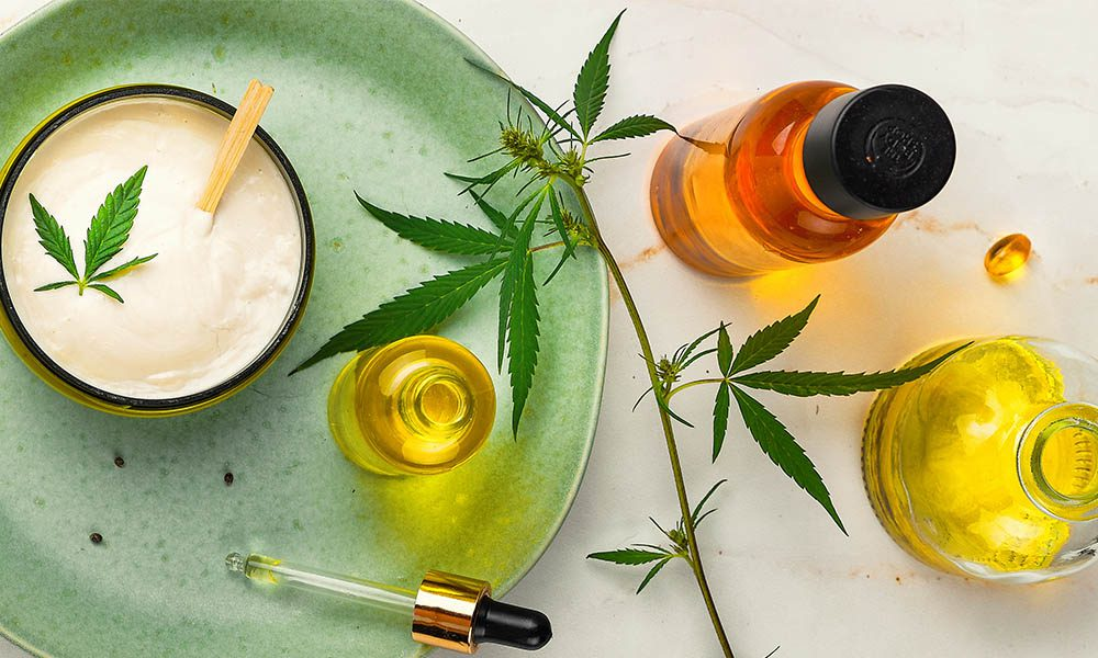 Blog - Cannabis Products Including CBD Oil, Mosterizer, and Pills Laying on a Table