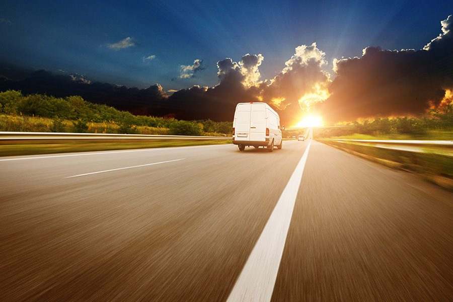 Cargo Insurance - White Cargo Van Driving Down the Road Into the Sunrise