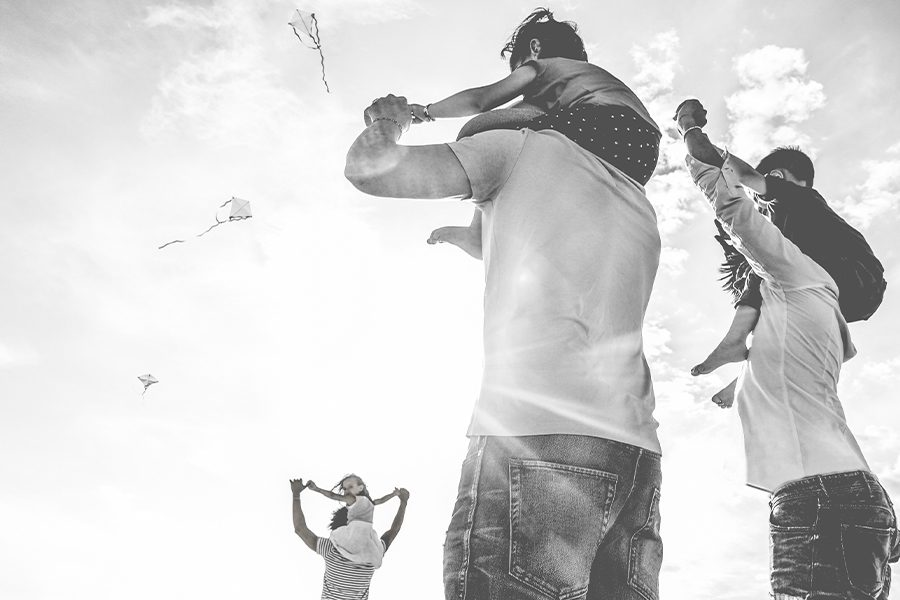 Personal Insurance - Couple at the Beach with Child on Shoulders in Black and White Looking Up
