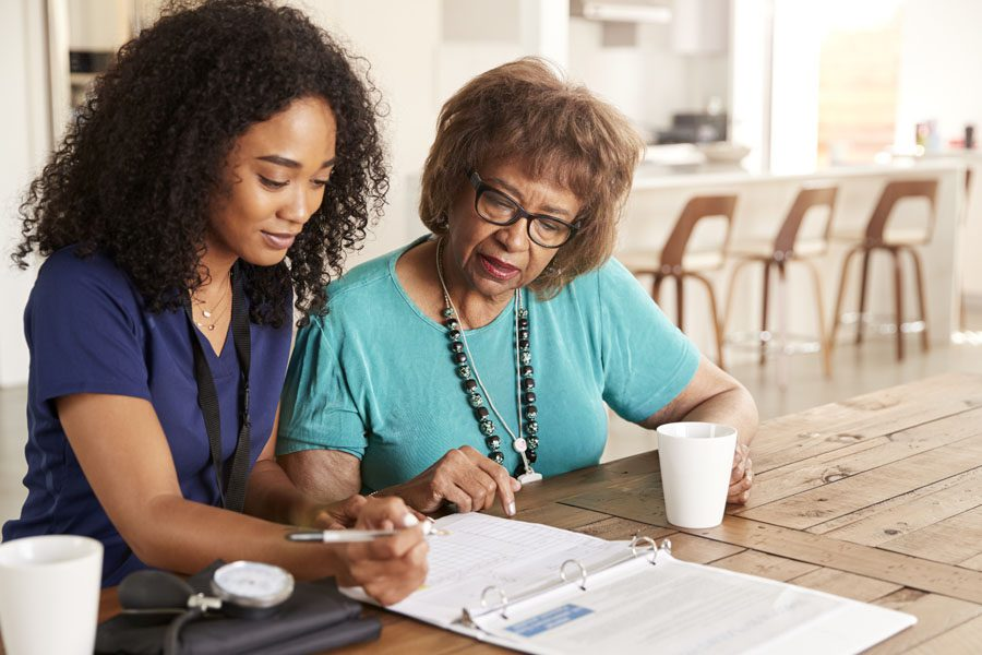 Medicare Supplement Insurance - Healthcare Worker Helping Fill Out Forms