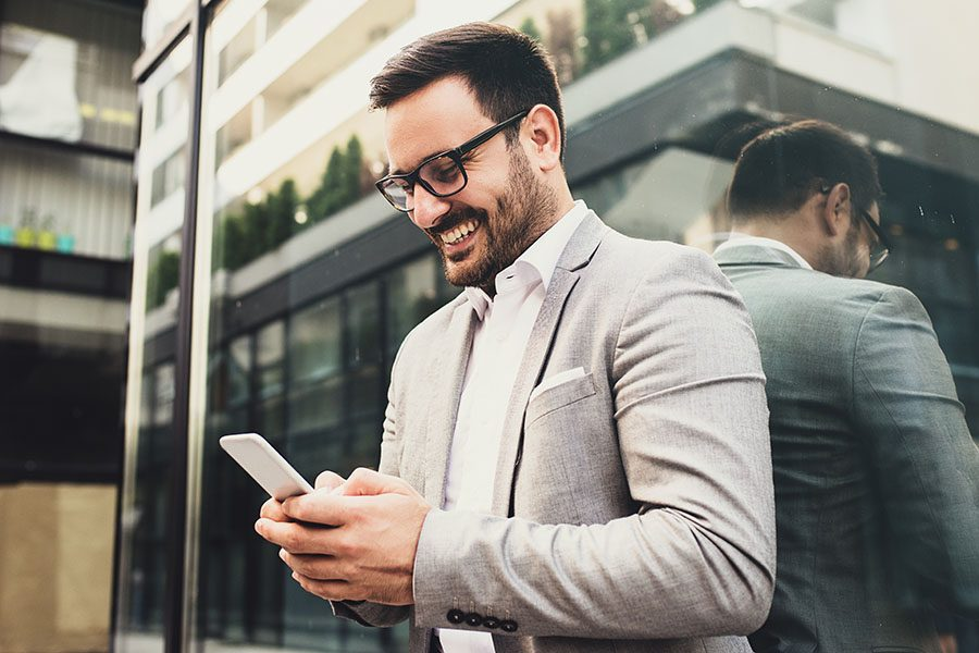 Client Center - Businessman Standing Outside Modern Office Building Using Phone