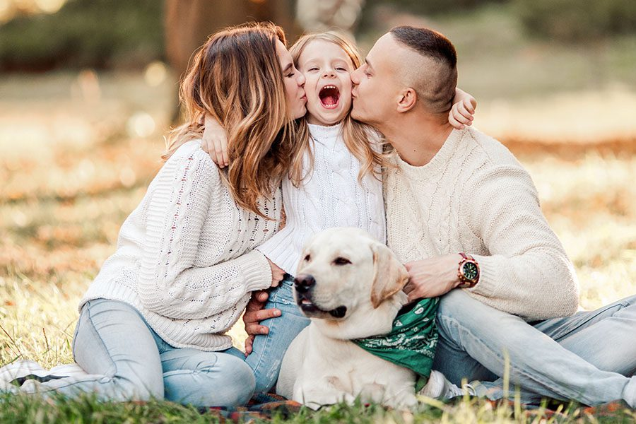 Personal Insurance - Happy Parents Kissing Their Daughter While Sitting Outside On Grass With Dog