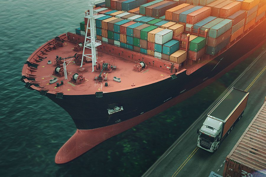 Specialized Business Insurance - Large Cargo Ship At Port Next To Shipping Containers And Truck