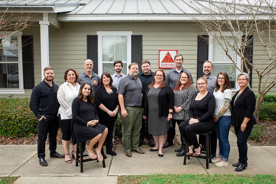 About Our Agency - Happy Team of Schneider and Associates Insurance Agencies Posing For a Group Portrait in Front of Office