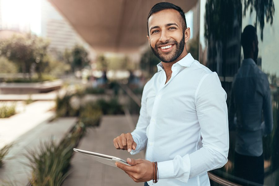 Client Center - Portrait of a Young Man Smiling and Holding a Tablet and Looking into Camera