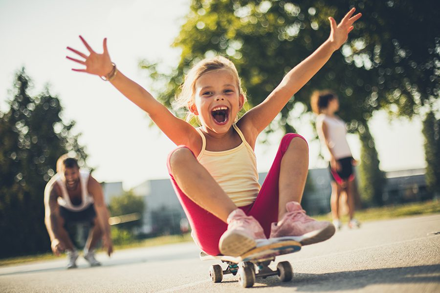 Employee Benefits - Little Girl Having Fun and Sitting on a Skateboard with Parents Blurred in the Distance on a Sunny Day