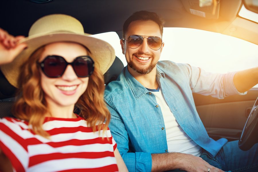 Personal Insurance - Happy Couple in Their Car Traveling in the Summer