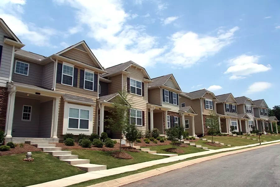 Homeowners-Association-Insurance-A-Row-of-Newly-Constructed-and-Professionally-Landscaped-Townhomes-on-a-Bight-Sunny-Day