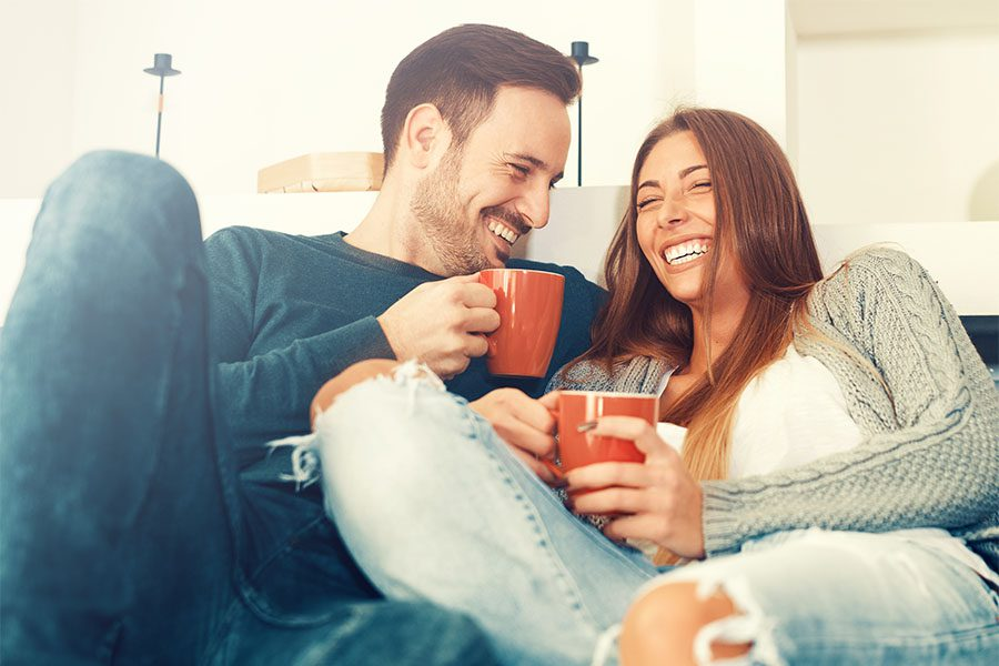 Client Center - Cheerful Young Couple Sitting at Home Enjoying a Cup of Coffee