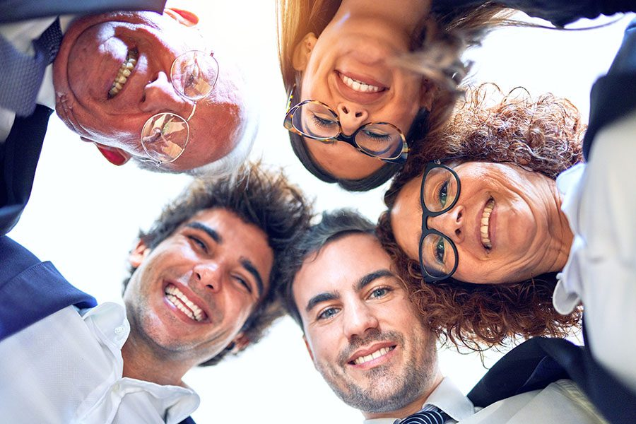 Employee Benefits - Portrait of Group of Smiling Employees Looking Down