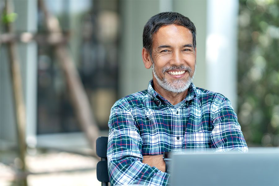 Insurance Quote - Smiling Mature Man Sitting Outside Using His Laptop