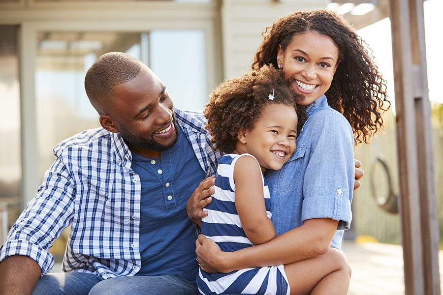 Personal Insurance - Portrait of Happy Parents Hugging Their Daughter Outside Their Home