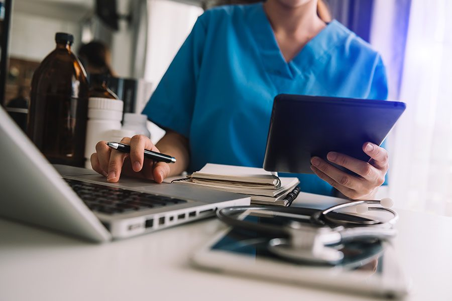 Specialized Business Insurance - Nurse Sitting In Medical Office Working On Tablet And Laptop