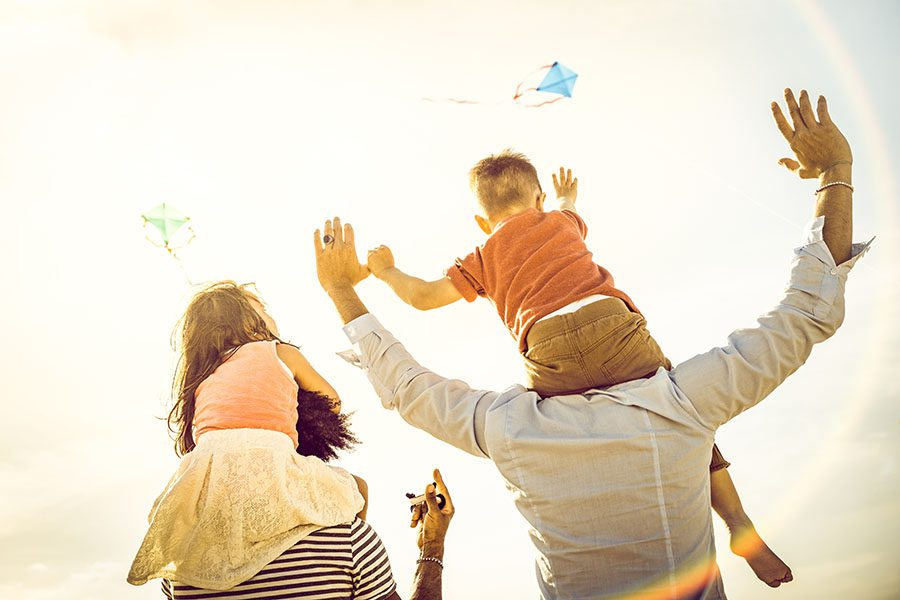 Insurance Quote - Happy Family Standing At The Beach Flying Kites