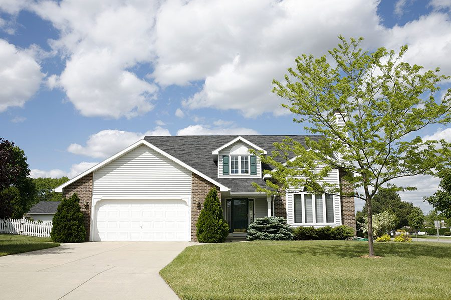 Home Insurance - Two Story Brick And Vinyl Home With Green Grass And Garage