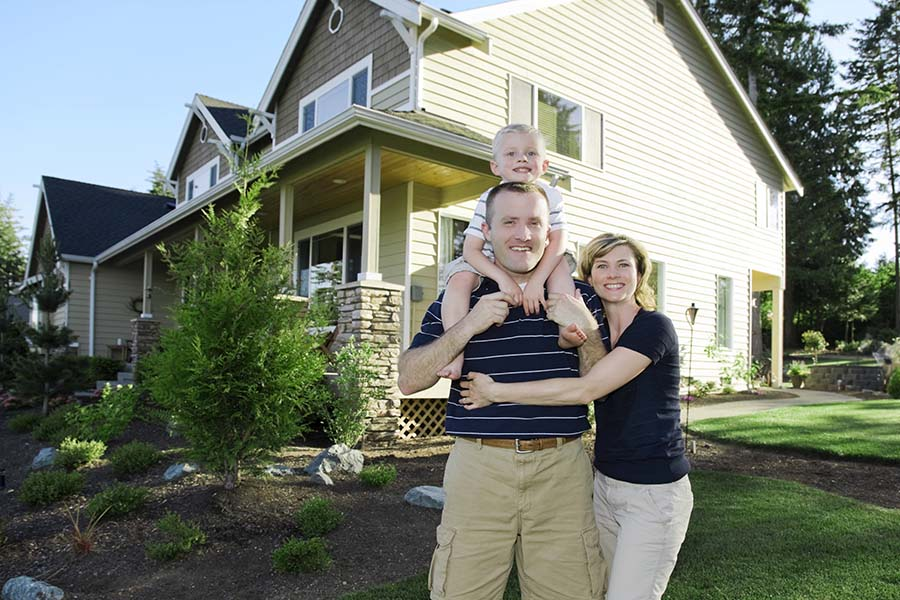 Personal Insurance - Portrait Of Happy Family With Toddler Standing Outside Their Two Story House