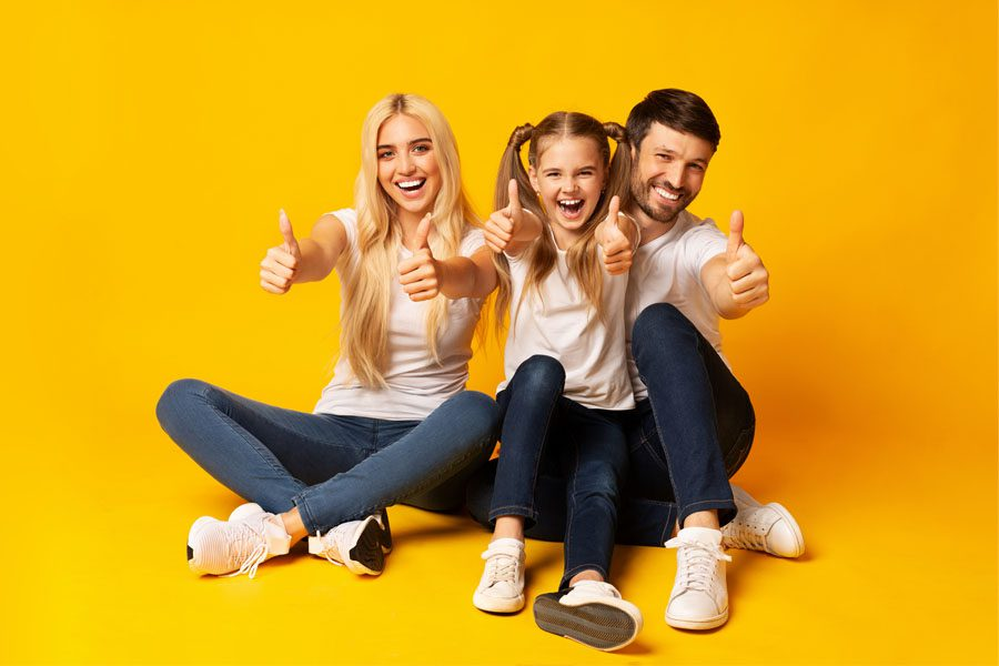 Thank You - Smiling Parents With Daughter Sitting And Giving Thumbs Up