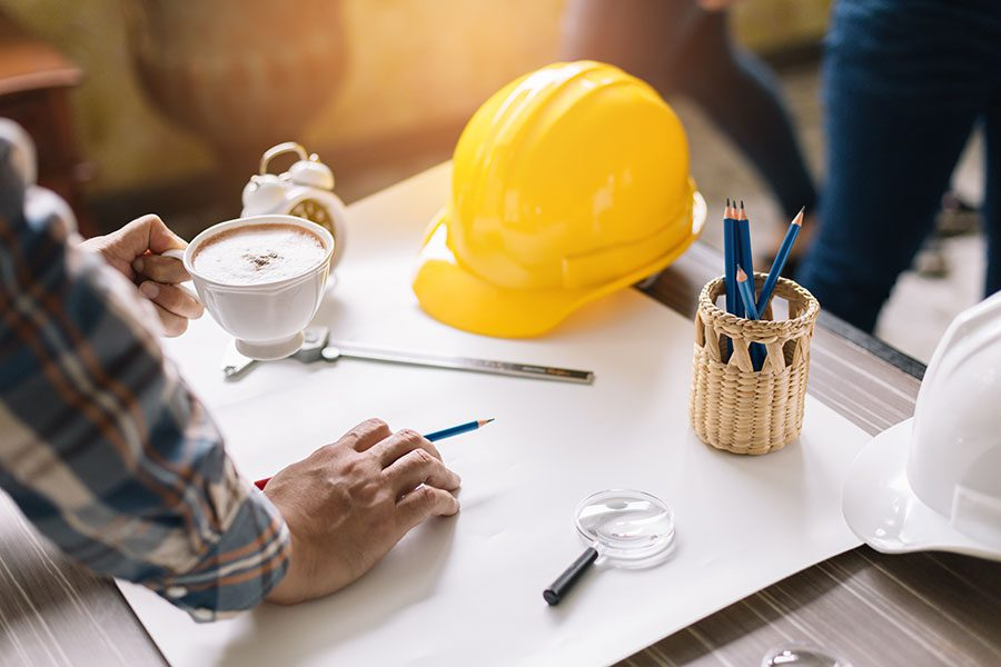 Specialized Business Insurance - Contractors Working on Desk with Papers and Yellow Hard Hat