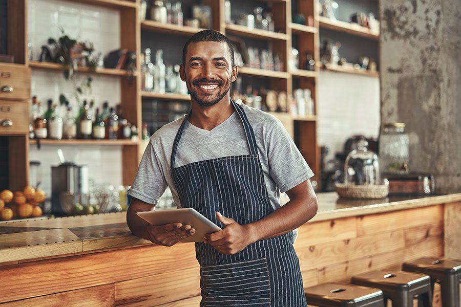 Business Insurance - African American Man Cafe Worker Holding iPad