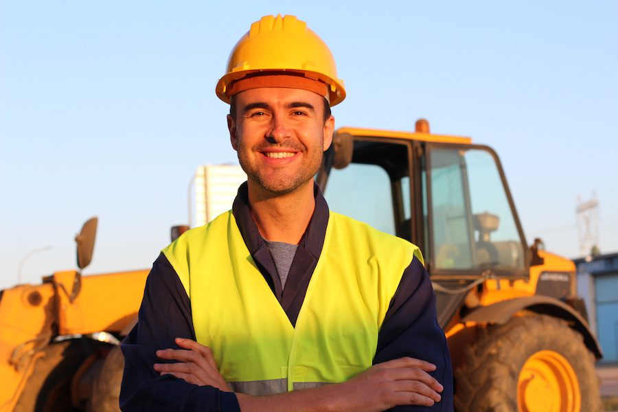 Contractor - Construction driver with excavator on the background