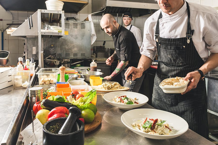 Specialized Business Insurance - Closeup View of Food, Utensils and Professional Chefs Cooking in the Kitchen of a Restaurant in a Hotel