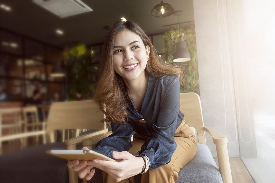 Contact - Smiling Businesswoman Sitting in Cafe Looking Out Window with a Tablet