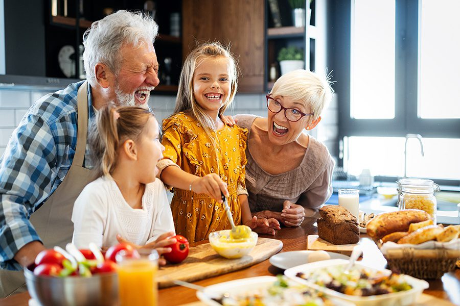 Personal Insurance - Happy Senior Couple Making Breakfast Together with their Grandchildren at Home in the Kitchen