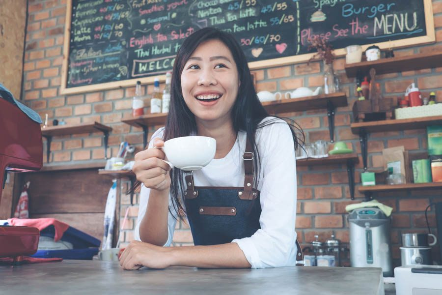 North Carolina Insurance - Small Business Owner Holding a Cup of Coffee in Her Coffee Shop