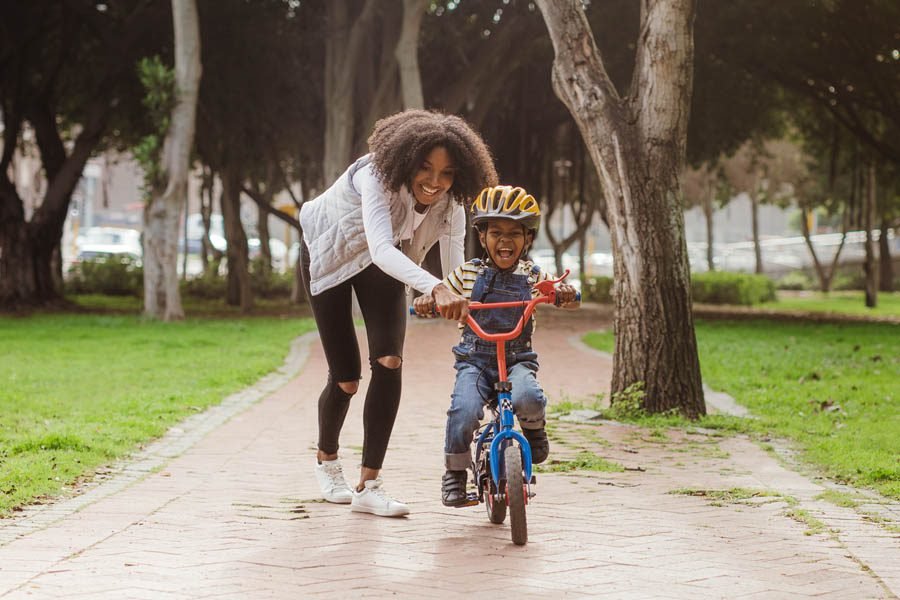 Personal Insurance - Mother and Son Riding a Bike Happily During a Rainy Summer